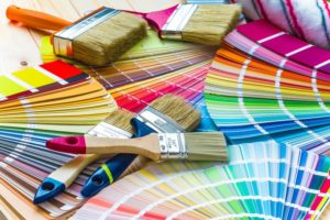 a pile of paint swatches and paint brushes
